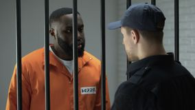 Prison guard giving black drug addicted male prisoner dose of white powder. Stock footage stock video