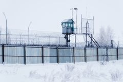 Prison guarding tower, fence with barbed wire.  stock photos