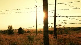 Prison or military fence of barbed wire at sunset close-up. Border zone, danger zone, security zone, fence of military. Unit and prison against sunset. The stock video footage