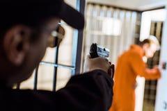 Prison officer aiming gun at escaping. Prisoner stock photo