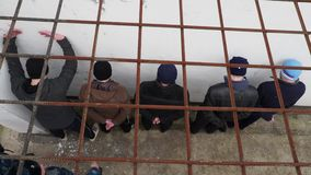 Prison officer searches a group of people in the courtyard of prison in Russia in the winter. A prison officer searches a group of people behind bars in the