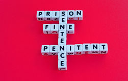 Prison sentence. Text ' prison, sentence, fine, penitent ' inscribed in black uppercase letters arranged crossword style on small white cubes, red background Stock Images
