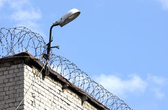 Prison wall. Detail of the brick prison wall with fence and lamp Royalty Free Stock Photography