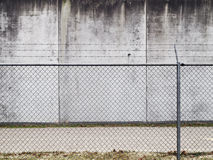 Prison wall. A barbed wired fence and concrete wall Royalty Free Stock Images