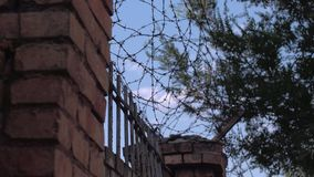 Prison wall and barbed wire. Barbed wire and prison on blue sky stock video footage