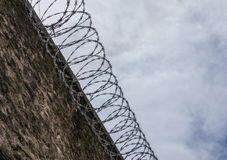 Prison wall with barbed wire. Concrete wall of the prison with cutting steel barbed wire Stock Photo