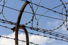 Prison wall barbed wire fence with blue sky in background Stock Photography