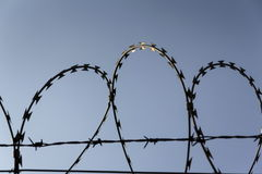 Prison wall barbed wire fence with blue sky in background. Prison wall barbed wire fence detail with blue sky in background Royalty Free Stock Image