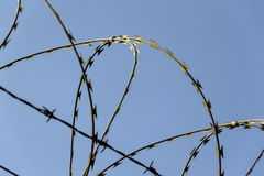 Prison wall barbed wire fence with blue sky in background. Prison wall barbed wire fence detail with blue sky in background Royalty Free Stock Images