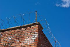 Prison wall with barbed wire. Prison wall with barbed wire on top Stock Image