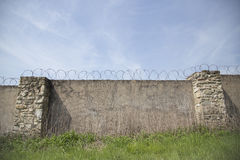 Prison wall with barbed wire. Prison walls with barbed wire lining the top Royalty Free Stock Photos