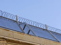 Prison warb wire. Prison wall and barb wire close up Stock Images