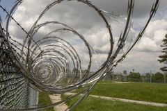 Prison yard fencing with razor wire. Close up of coiled razor wire on metal fence at abandoned prison yard Stock Photos