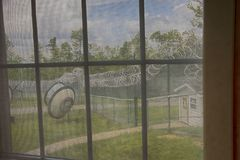 Prison yard with razor wire, guard house and satellite dish. View through bars on window from inside abandoned prison thourgh mesh and bars looking at yard with Royalty Free Stock Photos