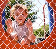 Prisoner. Young boy looking through fence playing prisoner Royalty Free Stock Image