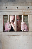 Prisoner. With a split lip holding the bars of his jail cell door Royalty Free Stock Image