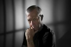 Prisoner. Senior prisoner in jail cell ponders his fate Royalty Free Stock Photo