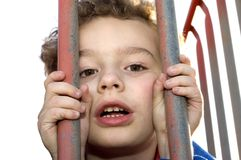 Prisoner. Young boy playing prisoner behind bars at playground Stock Images