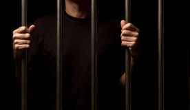 Prisoner. Hands of a prisoner behind bars Royalty Free Stock Photos