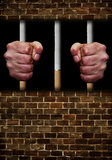 Prisoner of addiction. Prisoners hands in jail window holding on to cigarette bars Royalty Free Stock Photo