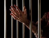 Prisoner behind bars Stock Photo