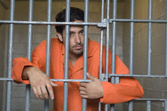 Prisoner Behind Bars. Portrait of prisoner standing behind prison bars Stock Photography
