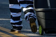 Prisoner Community Work. Prisoner doing community work in the county during a parade Stock Photo