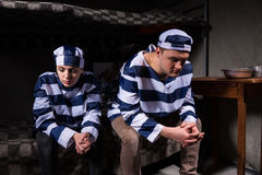 Prisoner couple wearing prison uniform have lost in thoughts in Royalty Free Stock Photos