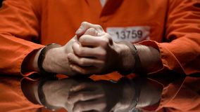 Prisoner in handcuffs clenching fists, denying quilt, interrogation room stock image