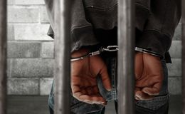 Prisoner in handcuffs in jail. Prisoner in handcuffs trapped in jail Royalty Free Stock Image