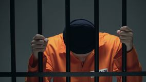 Prisoner holding bars and leaning head, feeling depressed, psychological rehab. Stock footage stock video