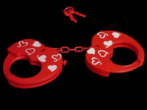 Prisoner of the love. Heart and Hand cuffs isolated on black background Stock Photo