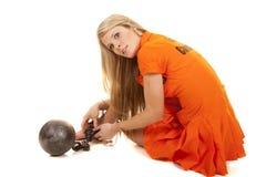 Prisoner orange ball cuffs sit look back Stock Image