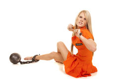 Prisoner orange ball cuffs sit mad. A woman in her orange jump suit trying to get out of her hand cuffs Stock Photos