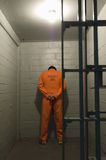 Prisoner In Prison Cell. Prisoner standing against the wall in prison cell Stock Photo