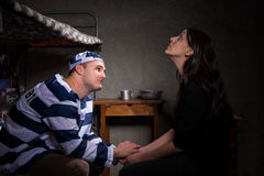 Prisoner sitting on a bed and holding female hand Stock Images