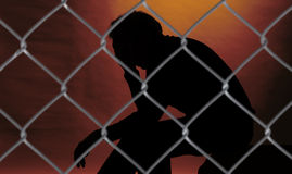 Prisoner. Sitting behind steel net, red light Stock Photo