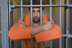 Prisoner Standing Behind Bars stock photos