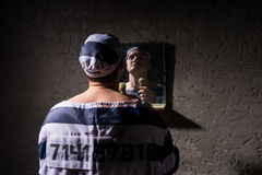Prisoner standing with shave brush and looking at his reflection Stock Image
