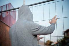 Prisonnier à capuchon d'homme avec la main sur une maille en métal Photos stock