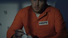 Prisonnier caucasien regardant avec dégoût la nourriture, conditions terribles en prison banque de vidéos