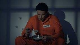 Prisonnier contrarié regardant avec dégoût la nourriture peu appétissante, conditions pauvres banque de vidéos