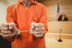 Prisonnier dans des poings de serrage de menottes Photographie stock