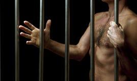 Prisonnier derrière des bars image stock