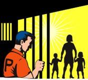 Prisonnier derrière des bars avec le famille Photos stock
