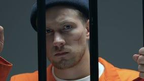 Prisonnier sûr avec des cicatrices sur le visage montrant des mains dans des manchettes sur la caméra, cellule clips vidéos