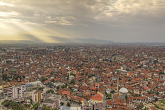 Prisren in Kosovo at sunset. City scape of second biggest city Prizren in Kosovo at sunset with red roofed houses and mosques. In the background a mountain range Stock Images
