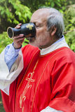 Priest drinking wine from sacred chalice Royalty Free Stock Images