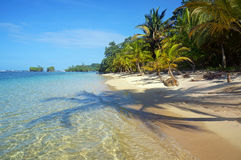 Pristine beach with shade of coconut trees. On the sand and islands in background Stock Images