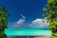 Pristine beach on tropical island day framed by green trees Royalty Free Stock Image